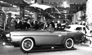 And indeed, here's the brand-new Renault Caravelle (note the scoops just ahead of the rear wheels), ready for launch by a young Sammy Davis, Jr. The photo flatters the late Sammy, but the stand propping up the Caravelle makes it look shorter and taller than it really was. Note the available hardtop hanging overhead.