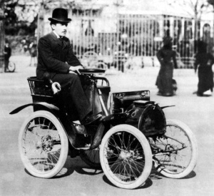 Figure 1. Louis Renault driving his original prototype automobile about 1900. The tiller steering has been replaced with a steering wheel. (Source: Renault by Hector MacKenzie-Wintle, Sutton Publishing Ltd., 1998)